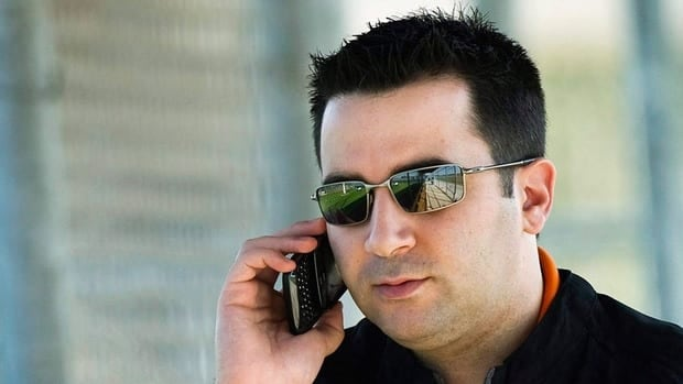 Toronto Blue Jays general manager Alex Anthopoulos talks on his cell phone during baseball spring training in Dunedin, Fla.