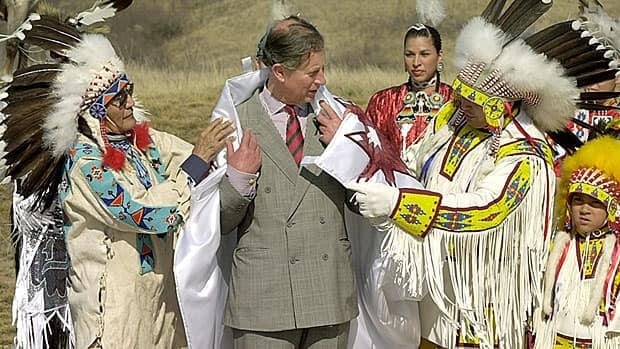Prince Charles participates in a Cree naming ceremony with elder Gordon Oakes (left) and Chief Perry Bellegarde in April 2001. His Cree name is Kisikawpisim Kamiyowahpahmikoot: The sun watches over him in a good way.