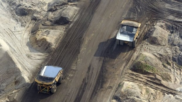Trucks drive along a road at an oilsands mine facility near Fort McMurray, Alta. Sunshine Oilsands is in talks with an international partner to develop two oilsands fields in the area.