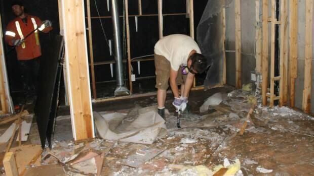 Amanda Pawlitzki's husband, Ryan, and his brother, right, doing demolition work on the couple's basement.