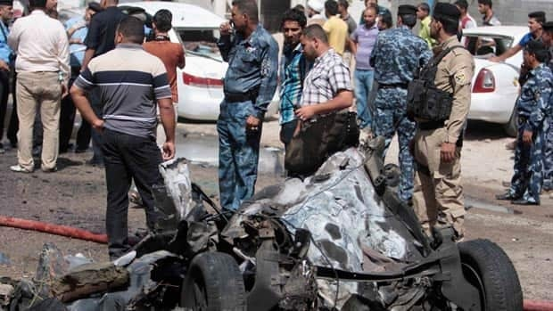 Iraqis gather at the scene of an explosion in Basra, 420 kilometres southeast of Baghdad, on Sunday. Two car bombs exploded in the predominantly Shia city, killing at least five people and wounding 10.