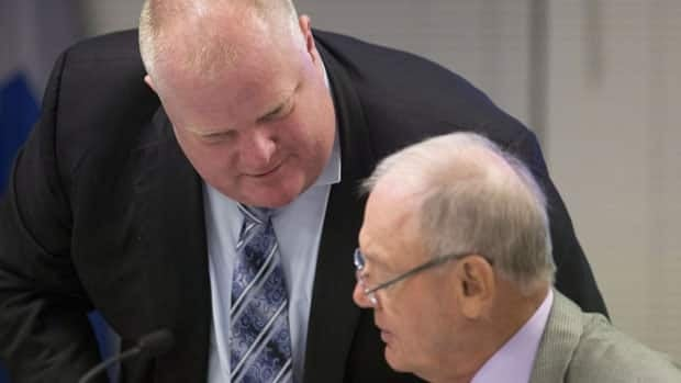 Toronto Mayor Rob Ford, left, shown conferring with Deputy Mayor Doug Holyday. Holyday says the longer the alleged crack cocaine video fails to materialize, the less credibility the story has.