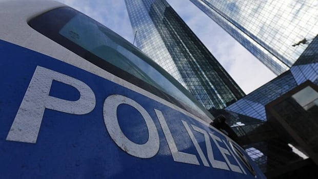 Police vehicles are parked outside the headquarters of Germany's largest business bank, Deutsche Bank, which is being probed as part of a tax scam involving carbon credit trading.
