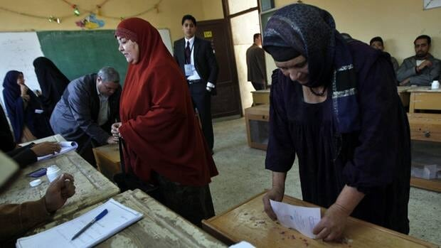 An Egyptian woman casts her vote as another checks for her name at a polling centre during the third round of the elections for Egypt's parliament, in Qalyobeia, Egypt on Jan. 3, 2012.