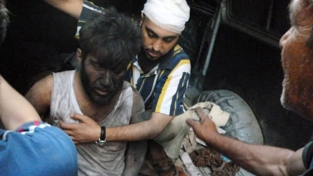 A man is helped at a site hit by what activists say was a missile attack from the Syrian regime in Homs last month. Human Rights Watch says it has investigated nine apparent missile attacks that killed at least 215 people, half of them children.