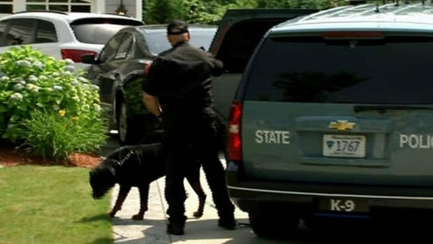 In this image taken from video, a state police officer and dog arrive outside the home of Aaron Hernandez on Saturday in North Attleboro, Mass.