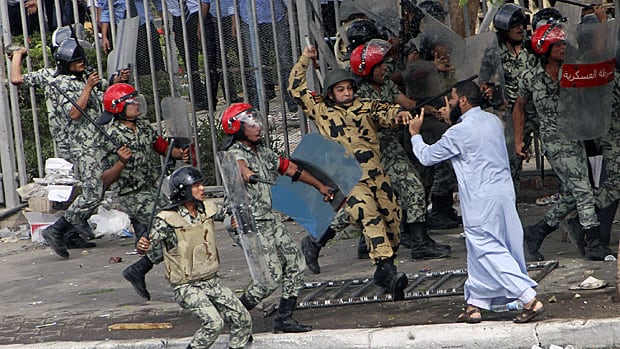 Egyptian soldiers raise their batons at a protester during clashes outside the Ministry of Defense in Cairo.