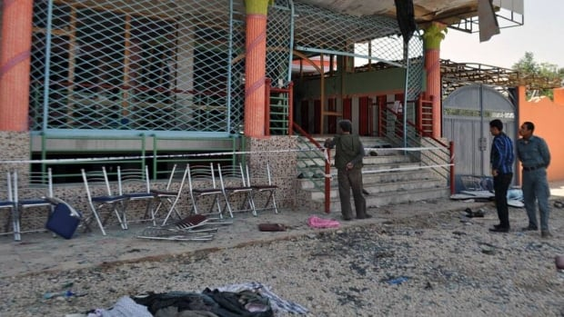 Onlookers and police examine the entrance of a damaged wedding hall where a suicide bomber detonated himself Saturday, killing a prominent Afghan MP and 22 others.
