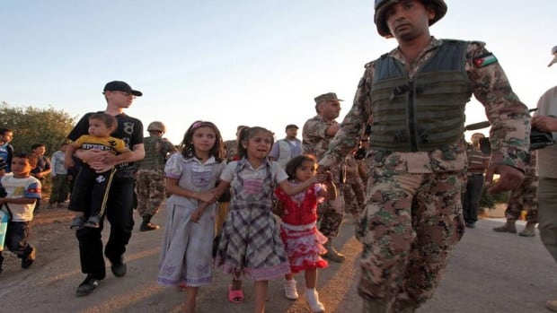 Syrian refugee children are helped by Jordanian soldiers after crossing the border