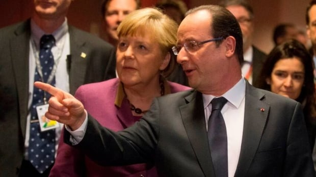 German Chancellor Angela Merkel and French President Francois Hollande arrive together for their press conferences at the end of the EU Budget summit. European Union leaders have agreed to a a significantly reduced budget that represents the first decrease in a budget in the union's history.