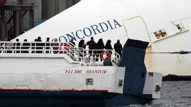 Relatives of the 32 victims of the Costa Concordia shipwreck pass near where the ship is leaning on its side, off the Tuscan island of Isola del Giglio, Italy, on Jan. 13, 2013.