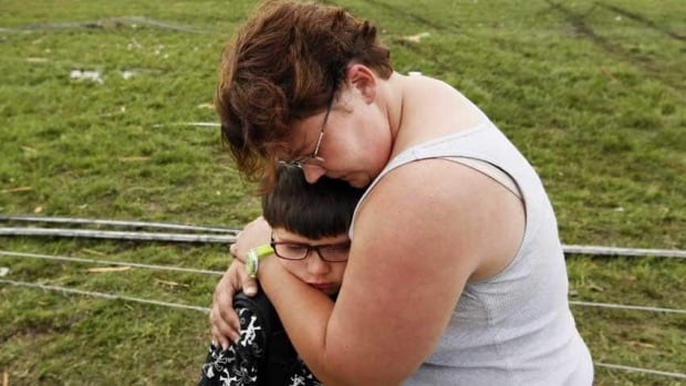 Rebekah Stuck hugs her son, Aiden Stuck, 7, after she found him in front of his elementary school, which was destroyed after a tornado struck south Oklahoma City and Moore, Okla.