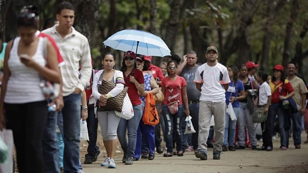 People stand in line outside the military academy for an opportunity to view Venezuela's late President Hugo Chavez lying in state.