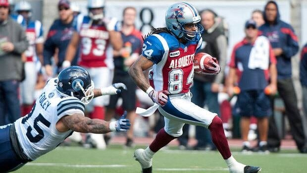 Montreal's Trent Guy, right, eludes a tackle attempt by Toronto's Ricky Foley to score a touchdown in the first half.
