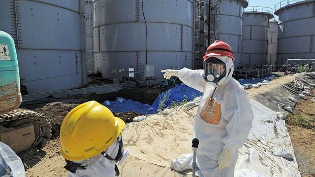 Japanese Trade Minister Toshimitsu Motegi, right, in protective gear at the Fukushima Dai-ichi nuclear plant at Okuma in Fukushima prefecture, northern Japan.