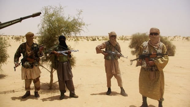 In this April 2012 file photo, fighters from Islamist group Ansar Dine stand guard during a hostage handover in the desert outside Timbuktu, Mali.