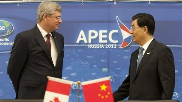 Prime Minister Stephen Harper speaks with Chinese President Hu Jintao at the APEC Summit in Vladivostok, Russia, on Sunday, September 9, 2012.