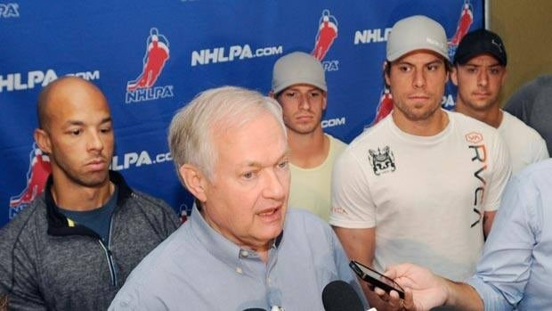 Donald Fehr speaks to reporters, flanked by NHLPA members such as Shea Weber, right, and Manny Malhotra.