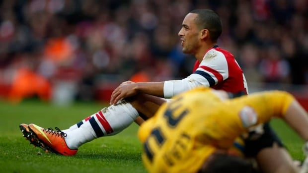 Arsenal's Theo Walcott sits up after competing for the ball with Blackburn Rovers' goalkeeper Jake Kean, right, during the English FA Cup fifth round soccer match in London on Saturday.