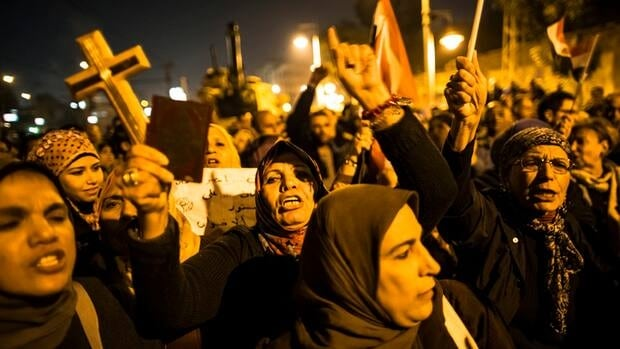 A woman holds up a Koran and a cross in her hand as Egyptian protestors opposing President Mohammed Morsi chant slogans during a demonstration at the Presidential Palace in Cairo on Tuesday.