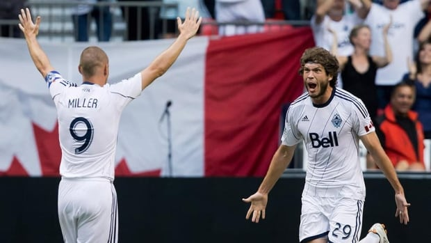 Vancouver Whitecaps' Tom Heinemann, right, celebrates his game-tying goal with teammate Kenny Miller against Chivas USA on Sunday.
