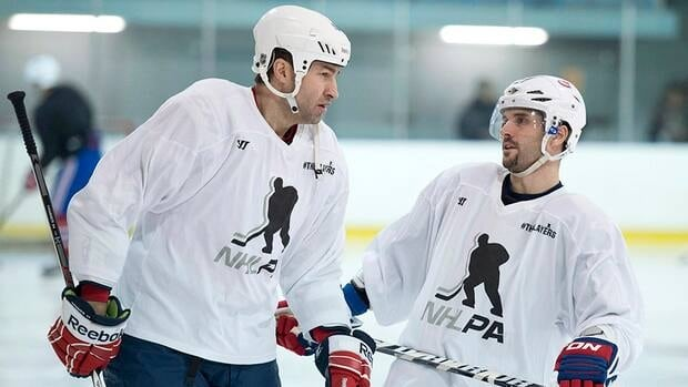 Montreal Canadiens captain Brian Gionta, right, chats with Washington Capitals Roman Hamrlik during an informal practice on Tuesday. Gionta and Hamrlik will be able to begin practicing with teammates soon as training camps are expected to open Sunday.