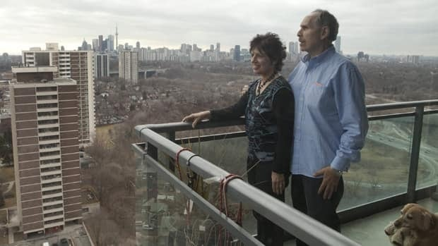 Joel and Debrah Weiss pose for a photo with their dog Sarah on the balcony of their Toronto condo.