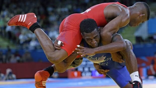 Livan Lopez Azcuy of Cuba competes with Haislan Veranes Garcia of Canada (in blue) during their 66-kg freestyle wrestling match at the 2012 Summer Olympics, Sunday, Aug. 12, 2012, in London. Olympic Committee leaders dropped wrestling from the Olympic program earlier this week, a surprise decision that removes one of the oldest Olympic sports from the 2020 Games.