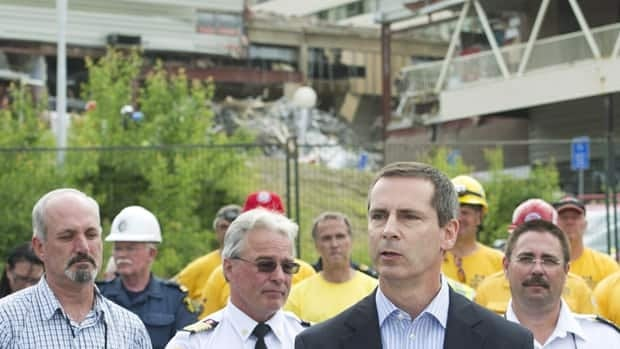 Ontario Premier Dalton McGuinty, centre, speaks to the community regarding the rescue and recovery of two bodies at the Algo Centre Mall in Elliot Lake, Ont., on Wednesday.