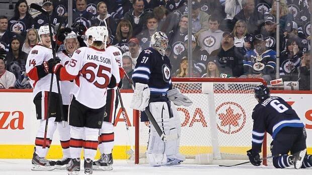 Ottawa Senators' Chris Neil (25), Colin Greening (14), and Erik Karlsson (65) celebrate Neil's goal against Winnipeg Jets' goaltender Ondrej Pavelec (31) and Ron Hainsey (6) during the second period in Winnipeg on Saturday.