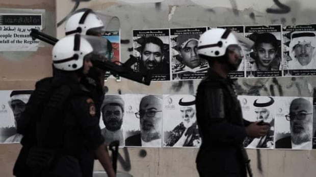 Pictures of people killed and jailed in the unrest are plastered on walls in Bahrain (Hasan Jamali/Associated Press)