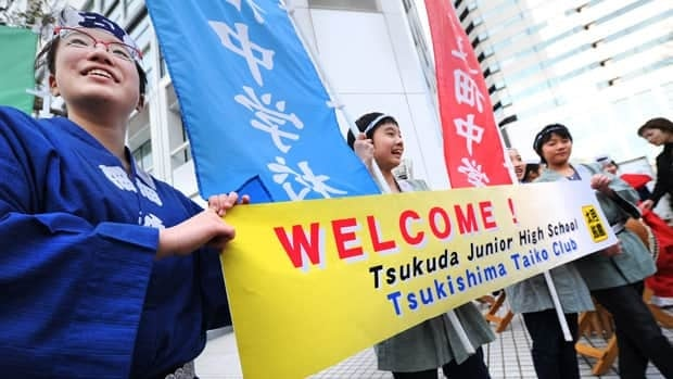 Clad in traditional costumes, junior high school students who are also members of a traditional drum band welcome members of the International Olympic Committee (IOC) evaluation commission in Tokyo.
