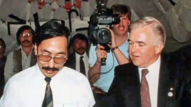 Former fisheries minister Tom Siddon, right, is seen signing an agreement while serving as an MP in 1990. He says the Harper government is covertly attempting to gut the fisheries act he helped shape.