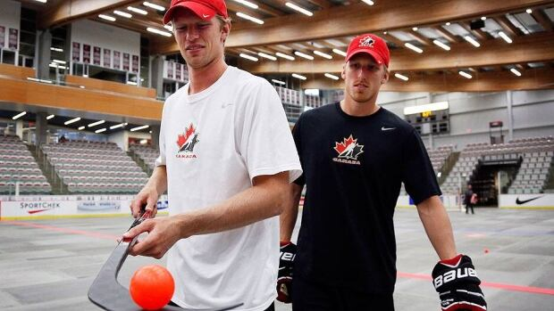 Eric Staal, left, balances a ball on his stick as his brother Marc looks on at the Canadian men's Olympic team orientation camp in Calgary. A third brother, Jordan, is also attending the camp in hopes of playing in Sochi in February.