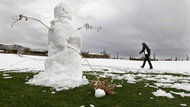 A spectator walks past a snowman made on a fairway after the first round of the Match Play Championship was suspended due to snow on Wednesday in Marana, Ariz.