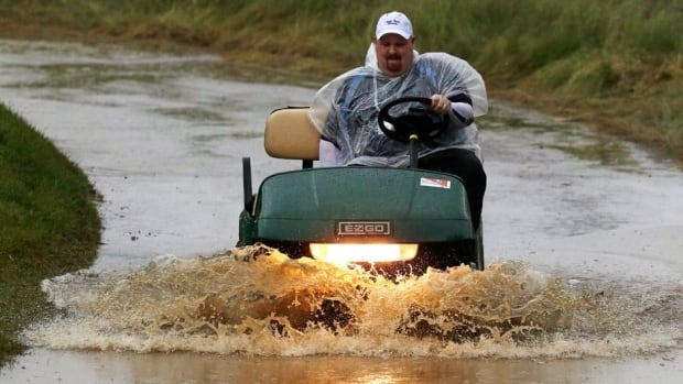 A golf cart makes its way through a flooded cart path as rain falls at Merion Golf Club, in Ardmore, Pa., early Monday.