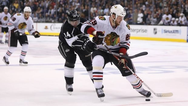 Bryan Bickell (29) of the Chicago Blackhawks plays the puck in the offensive zone as Justin Williams (14) of the Los Angeles Kings goes for the stick check in the third period of Game 4 on Thursday.