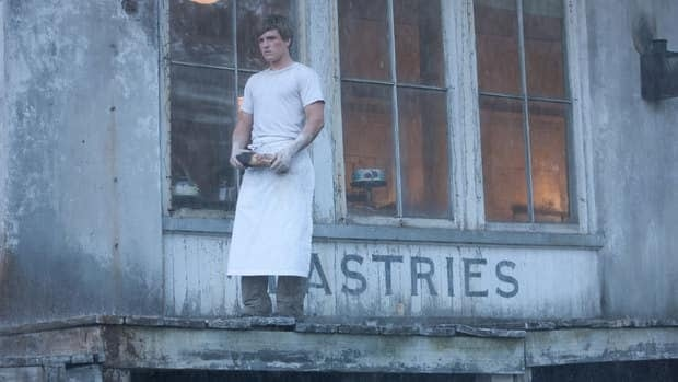 Actor Josh Hutcherson, as Peeta, stands outside the Mellark bakery in The Hunger Games. The North Carolina town where the film was shot is up for auction.