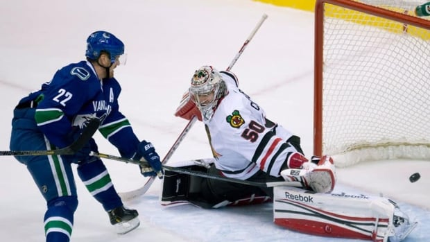 Canucks winger Daniel Sedin (22) scores on Chicago Blackhawks goalie Corey Crawford, right, during the second period Monday night at Rogers Arena in Vancouver.