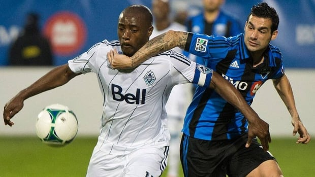Impact's Andrés Romero, right, and Whitecaps' Nigel Reo-Coker battle for the ball in the first half Wednesday of the Amway Canadian Championship soccer final in Montreal.