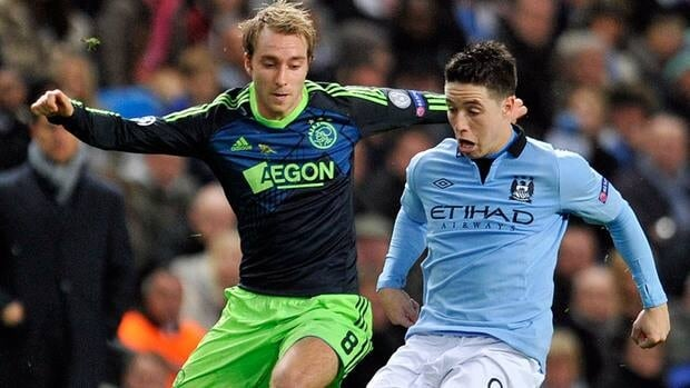 Manchester City's Samir Nasri, right and Ajax's Christian Eriksen, left, battle for the ball during their match at the Etihad Stadium in Manchester, England on Tuesday.