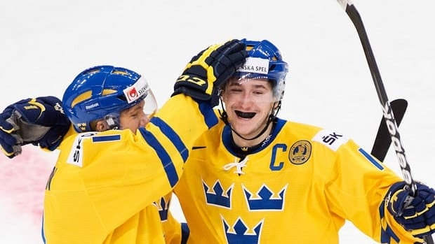 Sweden forward Filip Forsberg, right, celebrates his first-period goal with teammate William Karlsson. The Swedes blew a 2-0 lead but fought back for a 3-2 shootout win in the world junior hockey semifinals.