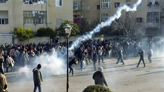 Protesters cover their faces from tear gas being fired in the Syrian city of Adlb on Dec. 30, 2011. The UN says more than 5,000 people have been killed in the country since March.