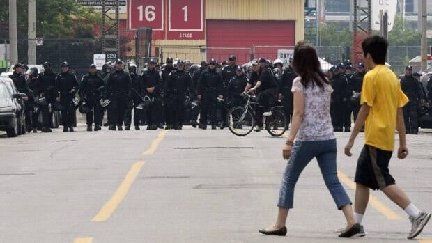 People walk across Pape Avenue as police officers in riot gear block the front of a temporary detention centre in Toronto on June 27, 2010.