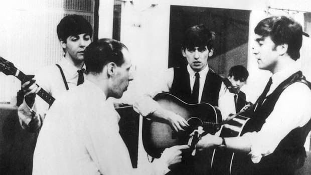 The Beatles are seen at a 1963 recording session with their producer George Martin, second from left.
