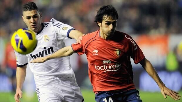 Real Madrid's Karim Benzema, left, duels for the ball with Osasuna's Alejandro Arribas, during their Spanish League match, at Reyno de Navarra stadium in Pamplona on Spain.
