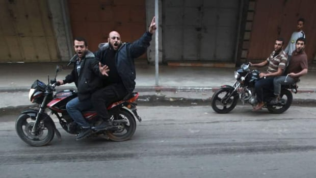 Palestinian gunmen ride motorcycles as the body of a man, who was suspected of working for Israel, was dragged through the streets of Gaza City on Tuesday.
