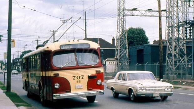 An old-school trolley bus moves through east-end Hamilton, no gas, no noise.