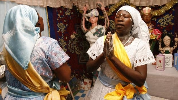 Eponon Adjoua Messouma, left, a priest of the traditional African Bosson religion prays with another follower of the faith at the altar of Mami Water in Aniassue, Ivory Coast. Ivory Coast has a per capita income of $1,387 and a life expectancy age of 55.4. Countries with such poor socioeconomic indicators tend to have the highest rates of religiosity, sociologists say.