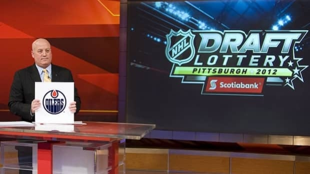 NHL deputy commissioner Bill Daly shows the winner of Tuesday's draft lottery in Toronto.